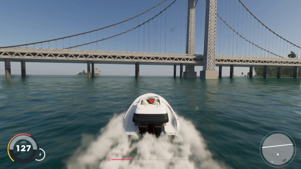 Racing a boat on open water toward a suspension bridge.
