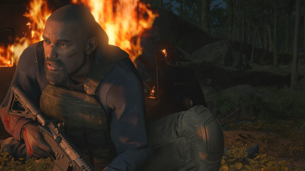 Cutscene with an NPC huddled behind cover with fire and explosions around him. There are no captions.